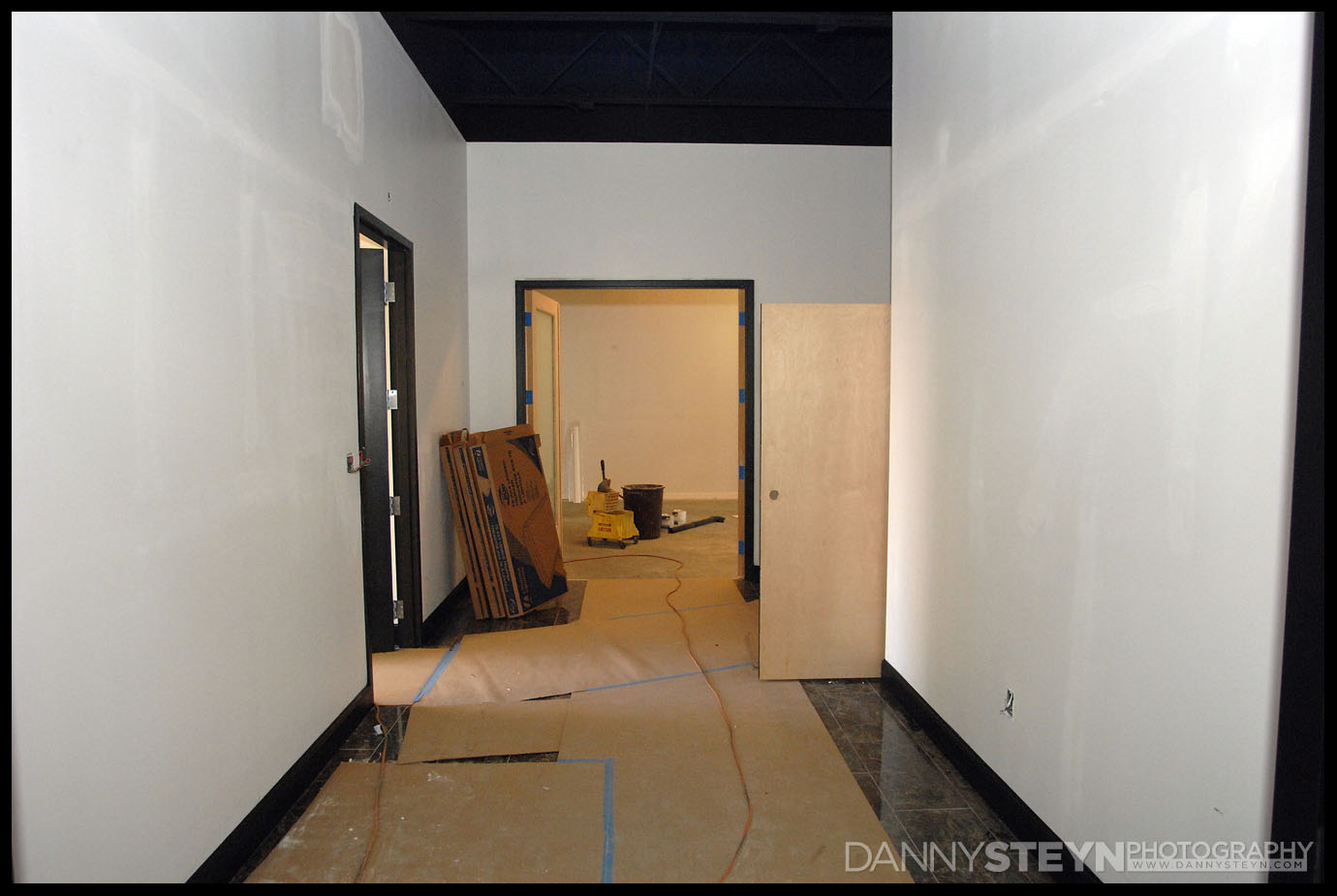 Photo Studio Gallery showing marble floor, black 8ft doors with frosted glass, and black baseboards.