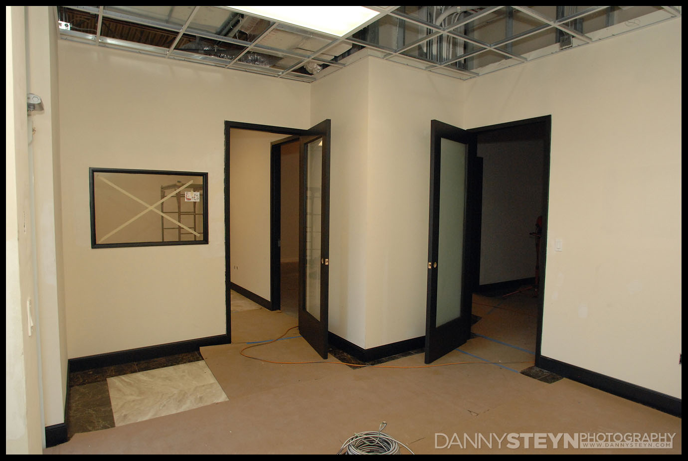 Photo Studio front Lobby showing tiles, black 8ft doors with frosted glass, and black baseboards. Lighting and drop ceiling being hung.